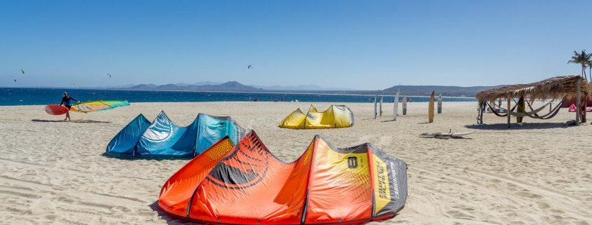 The beach at Vela Baja, a wide sandy beach with a palapa with hammocks, kites laying on the beach and a windsurfer walking to the water.