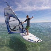 Young boy learning how to windsurf on clear blue sea